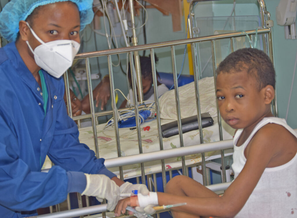 Darline with a young boy patient at St. Damien Hospital